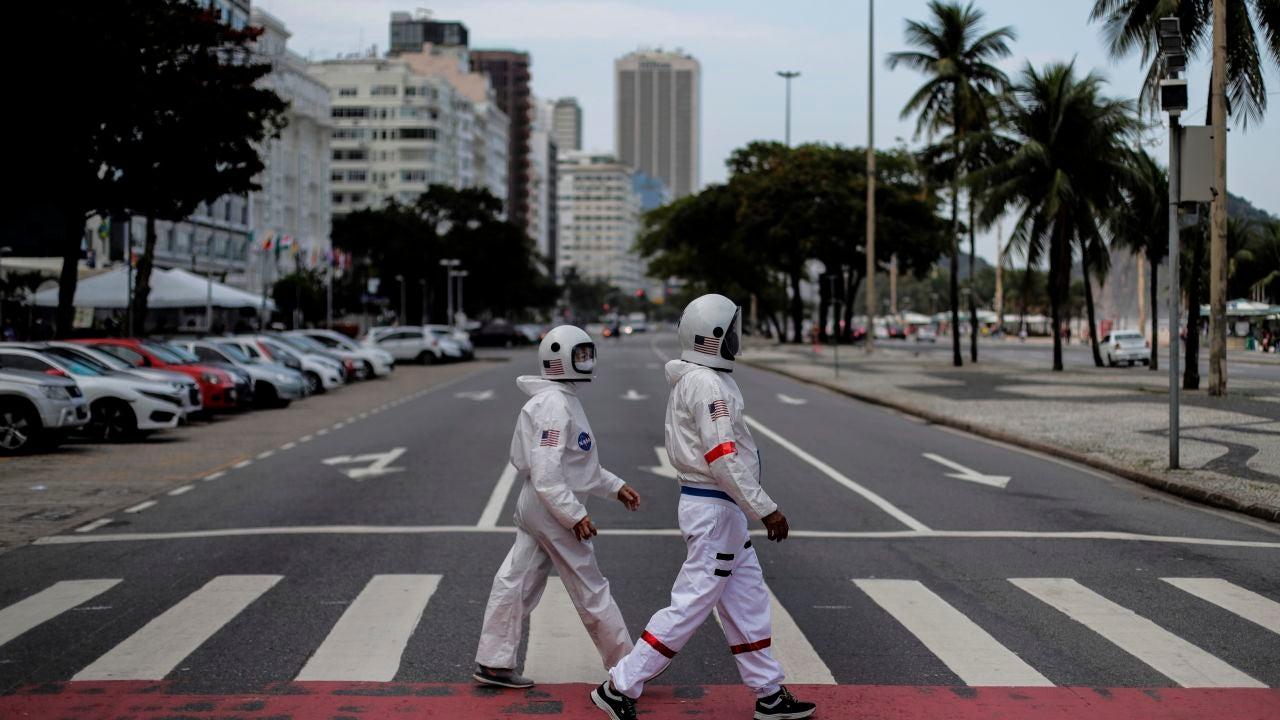 Tercio Galdino y su esposa, Alicea Galdino, caminan por la playa de Leme vestidos de astronautas