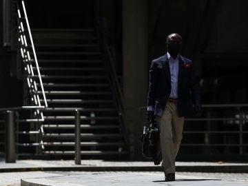 Un hombre pasea por Londres con una mascarilla