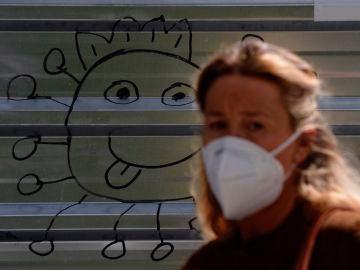 Una mujer con mascarilla pasea por la calle