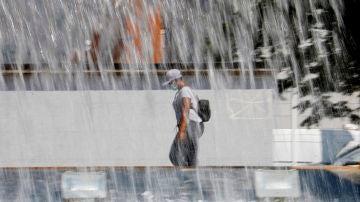 Una mujer pasa ante una fuente en Córdoba