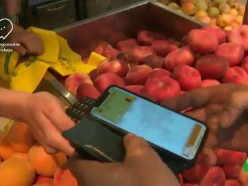 Imagen de una persona pagando con el móvil en una frutería