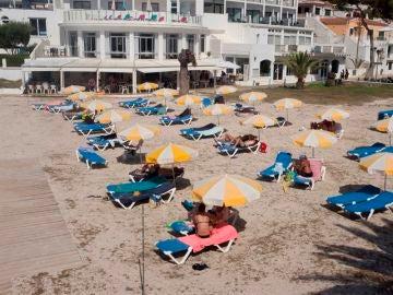 Varias personas toman el sol en la Cala Santandría de Menorca.