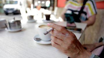Una mujer fuma en una terraza
