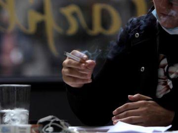 Una mujer fuma en una terraza.