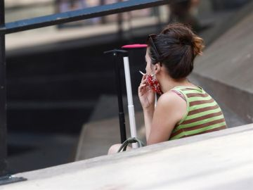 Una mujer fuma en la calle.