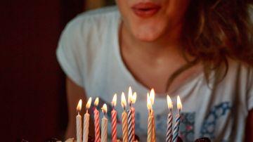 Imagen de archivo de una joven soplando las velas de una tarta