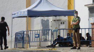 Un policía y un guarida de seguridad vigilan a un grupo de migrantes que consiguió saltar la valla.