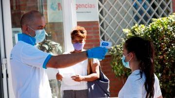 Un paramédico toma la temperatura a una ciudadana antes de acceder al centro de salud