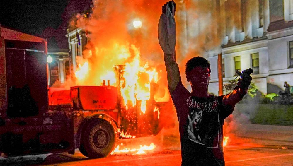 Un manifestante posa delante de un camión de basura en llamas durante la segunda noche de disturbios por los disparos a Jacob Blake en Kenosha, Wisconsin, EE. UU.