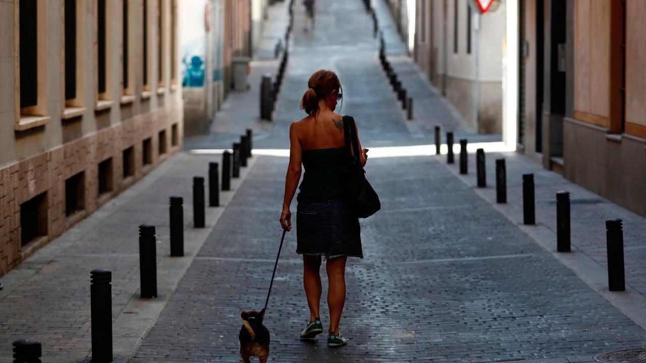 Una mujer pasea con su perro por una calle desierta del centro de Madrid
