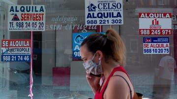 Una mujer con mascarilla pasa ante un comercio cerrado con varios carteles que anuncian su alquiler