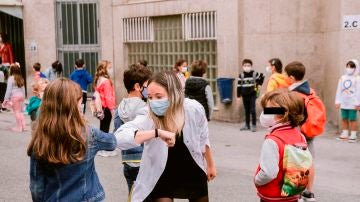 Una profesora realiza un saludo con el codo junto a una alumna