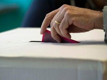 Una persona deposita su voto en una urna