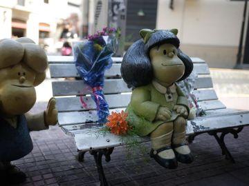 Flores junto a la escultura de Mafalda en Buenos Aires tras la muerte de Quino