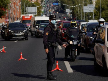 Un agente controla la movilidad en la salida de Madrid (Archivo)