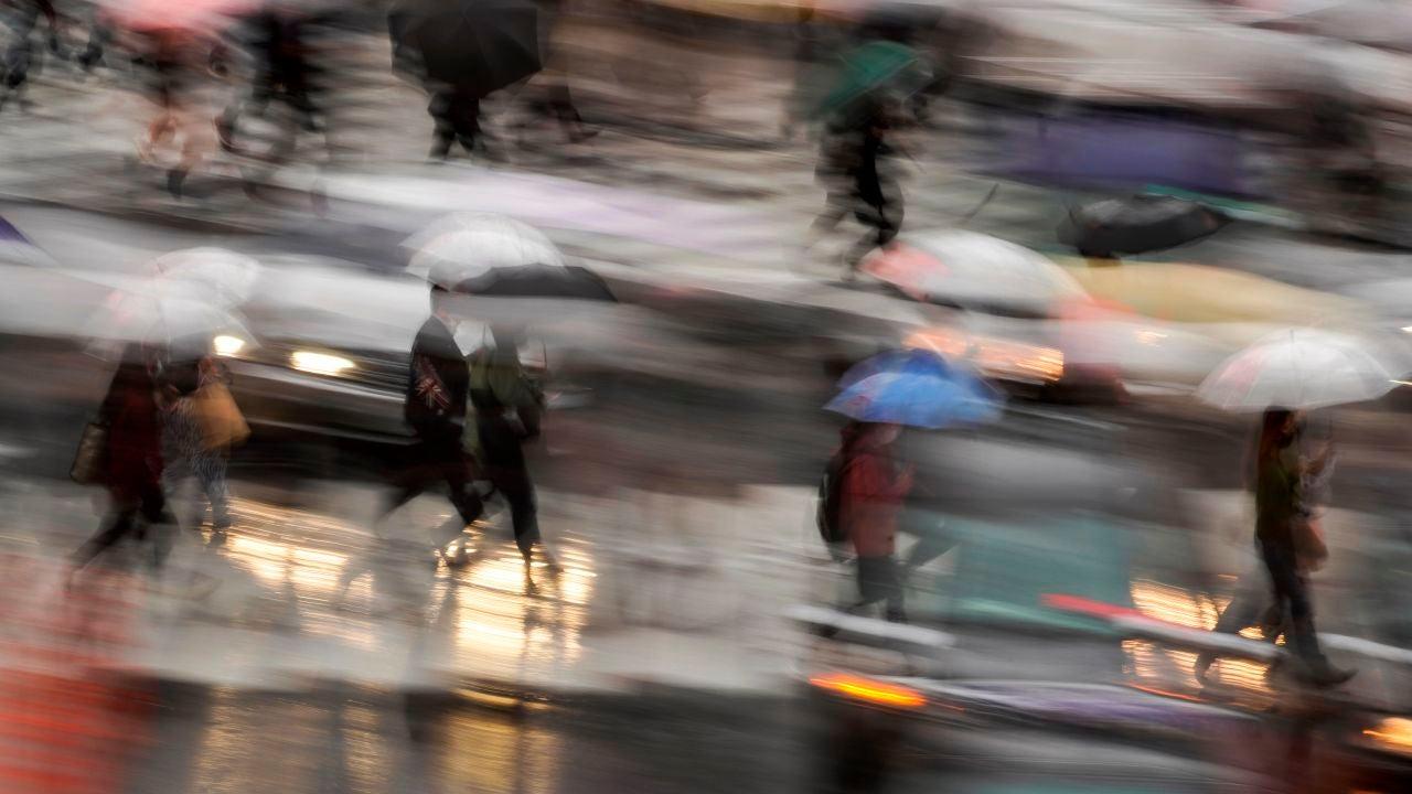 Fotografía tomada con velocidad de obturación lenta que muestra a peatones con paraguas en un cruce de Tokio, Japón