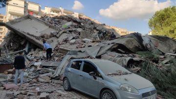 Dos personas buscan en los escombros tras el terremoto que ha sacudido Turquía.