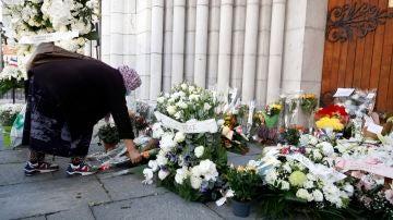 Una mujer deja una flor en recuerdo a las víctimas del ataque terrorista en Niza