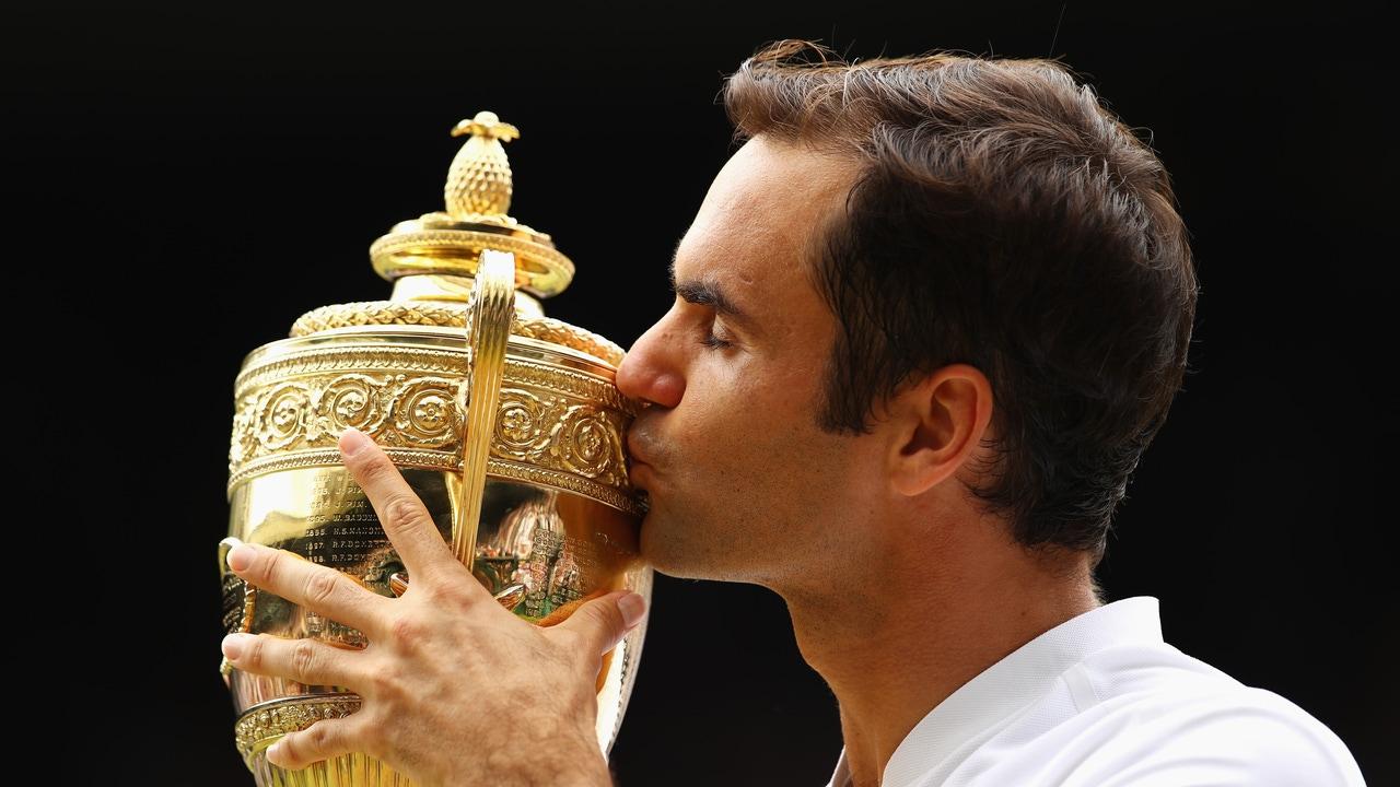 Roger Federer besando su título de Wimbledon