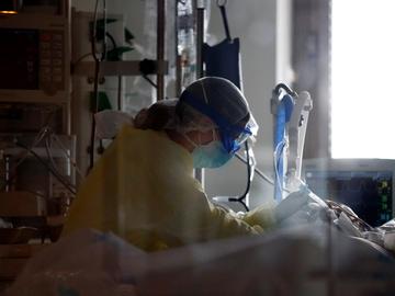 Un sanitario atiende a un paciente COVID en la UCI del Ramón y Cajal
