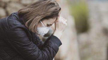 Una mujer con mascarilla sufre un ataque de ansiedad