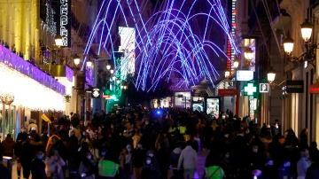 Personas se congregan para disfrutar de las luces navideñas en la calle de Preciados, este martes en Madrid.