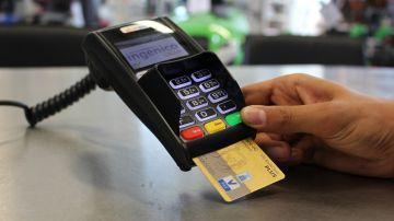 Una persona usa su tarjeta de crédito para una de sus compras.