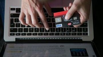 Una persona utiliza su tarjeta de crédito para pagar una compra online