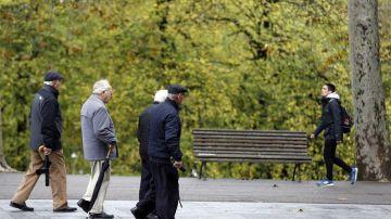 Jubilados y pensionistas pasean en un parque de Bilbao.