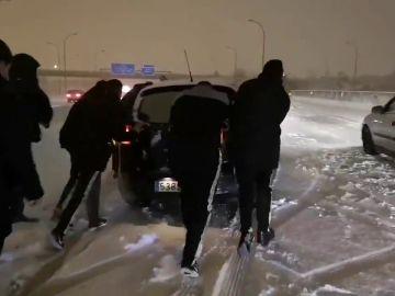 Jugadores del Rayo ayudando a un coche en la nieve