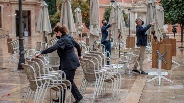 Unos trabajadores de un restaurante del centro de Valencia recogen la terraza.