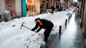 Un vecino retira nieve de la calzada en calle León de Madrid.