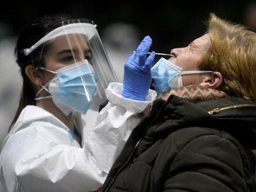 Imagen de una sanitaria realizando una PCR a una mujer