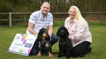 La pareja afortunada posa junto a sus perros y el cheque del premio