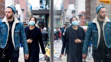Personas con y sin mascarilla caminan por una calle de Nueva York