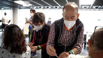 Dos personas reciben sus respectivas dosis de vacuna en el Wizink Center de Madrid.