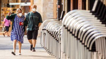 Dos personas con mascarilla por la calle