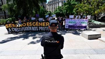 Un grupo de personas se manifiesta frente al Congreso de los Diputados, donde el pleno del Congreso debate este martes una proposición de ley trans