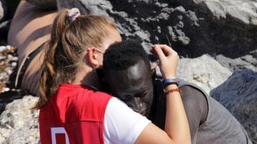 Una trabajadora de la Cruz Roja y un migrante que ha logrado cruzar uno de los espigones fronterizos de Ceuta este martes se abrazan.