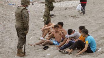 Miembros del Ejército de Tierra vigilan a un grupo de inmigrantes menores que han logrado cruzar uno de los espigones fronterizos de Ceuta