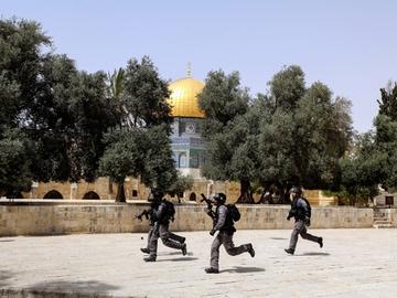 Agentes de la policía de Israel corren ante la explanada de la mezquita de Al-Aqsa.