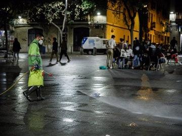 Un hombre riega una calle de Barcelona, una semana después del fin del estado de alarma, en Barcelona