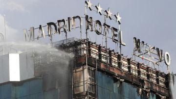 Bomberos extinguen las llamas tras un aparatoso incendio en la fachada exterior del Hotel Nuevo Madrid.