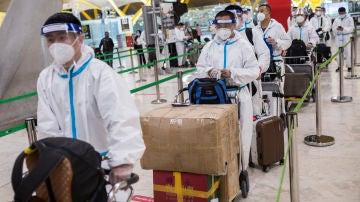 Viajeros procedentes de China con trajes de protección en la terminal T4 del Aeropuerto de Barajas