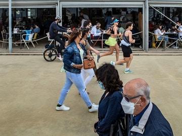 Varias personas pasean frente a un chiringuito del Paseo Marítimo de la Barceloneta