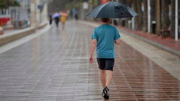 Un hombre camina este sábado bajo la lluvia