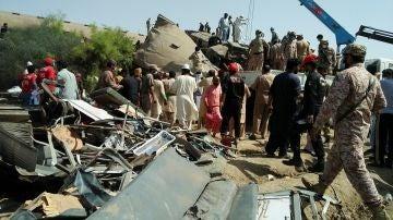 Soldados paramilitares y trabajadores de rescate se reúnen en el lugar tras una colisión entre dos trenes en Ghotki, Pakistán