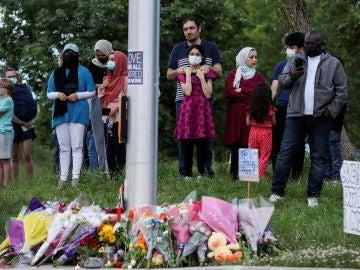 Un grupo de personas se reúne en el memorial creado en homenaje de la familia asesinada