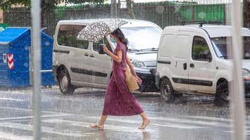 Una mujer camina en Logroño, un día de tormenta acompañada de granizo.