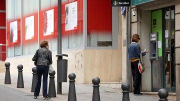 Una mujer saca dinero en un cajero automático de un banco mientras otra espera